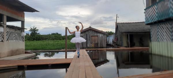 Menina faz balé sobre pontes construídas em cheia recorde do Rio Amazonas